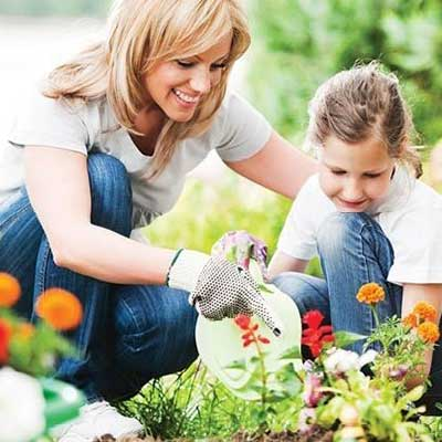 A mother and daughter working together in the garden.