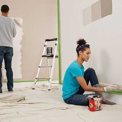 A couple painting a room.