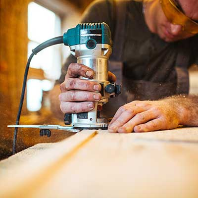 A person using a reciprocating saw.