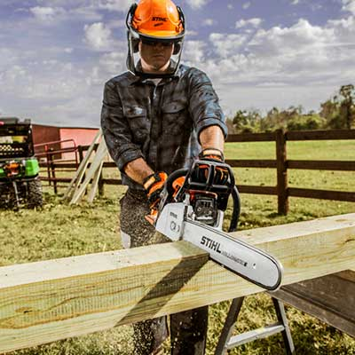 A person holding a chainsaw cutting wood.