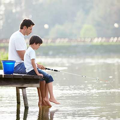 A father and son fishing on a dock.